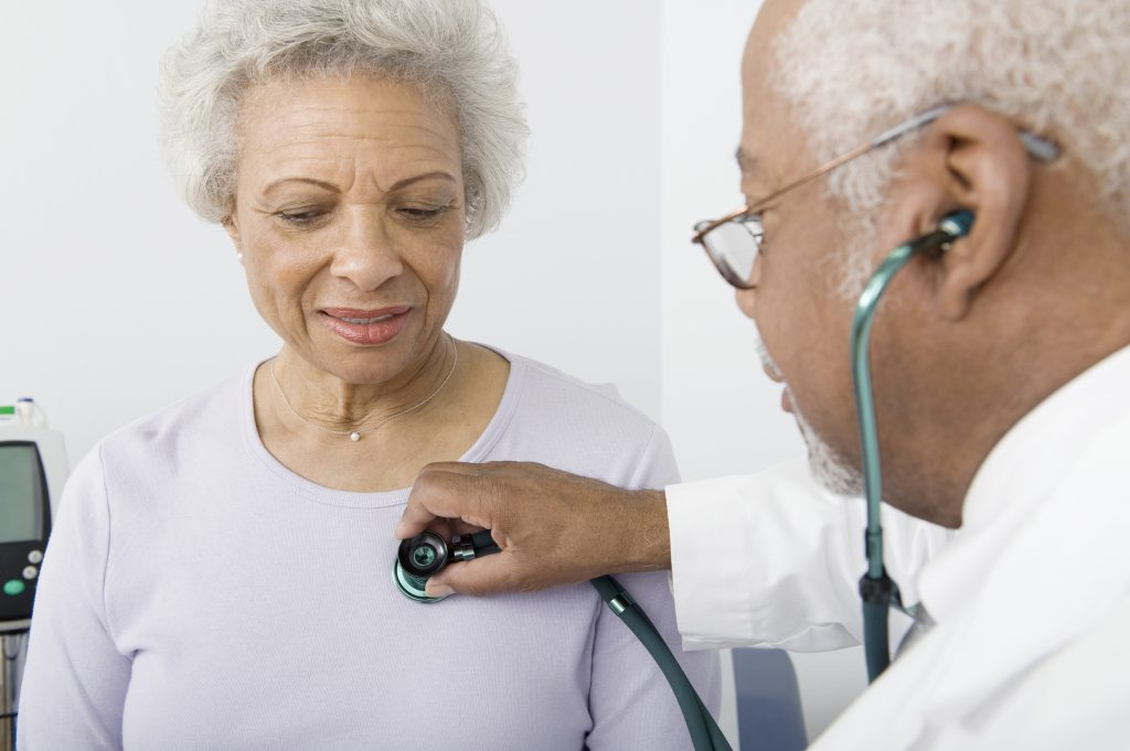 Doctor examines elderly female patient with stethoscope